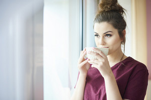 Attractive woman drinking coffee indoors
