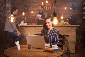 Attractive woman is reading good news from her business partner on her laptop in a coffee shop. Young freelancer. Modern Antrepreneur.