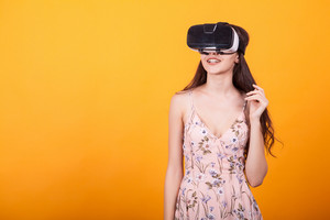 Attractive woman wearing virtual reality glasses. VR headse in studio over yellow background