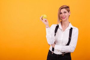 Attractive woman with blond hair keeping arms crossed and holding a green apple over yellow background. Tasty apple. Healthy fruit.