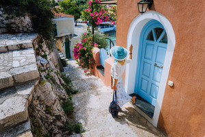Attractive young fashion woman on summer vacation on Kefalonia Island. Beautiful tanned woman with sun hat exploring small traditional touristy town, Greece, Europe