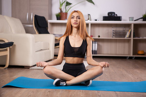 Attractive young girl sitting in lotus yoga position in her house. Relaxing state of mind.