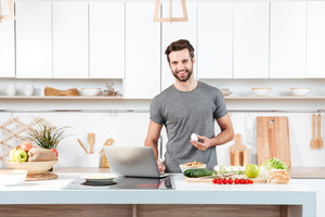 Attractive young man cooking with mixing bowl and looking at camera in the kitchen