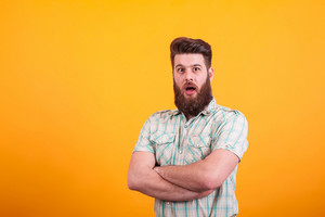 Attractive young man looking shocked with arms crossed over yellow background. Bearded man. Man expression.