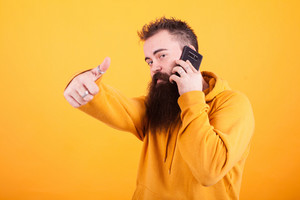 Attractive young man with long beard talking on the phone and showing thumbs up sign over yellow background. Hipster. Hand sign. Hoodie