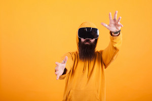 Attractive young man with long beard wearing virtual reality headset making hand gestures over yellow background. Modern vision. Handsome man. Yellow hoodie.