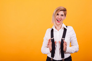 Attractive young woman acting funny in front of the camera over yellow background. Stylish hair. Red lipstick.