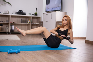 Attractive young woman doing lateral abs workout. Intens home training.