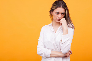 Attractive young woman in white shirt over yellow background. Facial expression