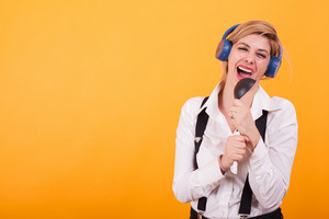 Attractive young woman singing on a black spoon with headphones on her head over yellow background. Cute woman. Modern woman.