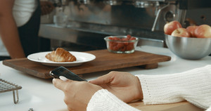Attractive young woman wearing a white sweater in a loft style bakery or coffee shop with a smartphone