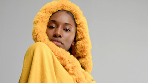 autumn look of black mixed race woman in yellow poncho in studio