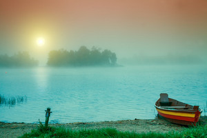 Autumn misty early morning. Wooden boat on the river bank