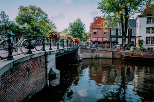 Autumnal Amsterdam canal scene with bicycles and bridge