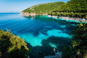 Azure bay. Picturesque scenery of the cove with turquoise calm water, surrounded by hills with cypresses, pine and olive trees. White limestone cliffs mirrow in the crystal clear water