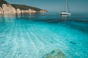 Azure blue lagoon with calm waves and drift sailing catamaran yacht boat. Rocky cliff coastline in background