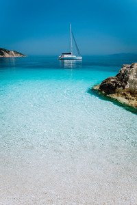 Azure blue lagoon with sailing catamaran yacht boat at anchor. Pure white pebble beach, some rocks in the sea