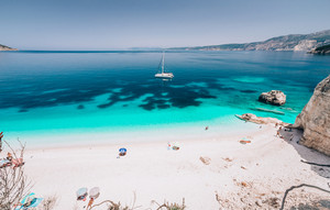 Azure water of Fteri beach, Cephalonia Kefalonia, Greece. White catamaran yacht in clear blue sea water. Tourists on sandy beach near azure lagoon