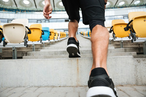 Back view close up of a male legs in sneakers running on a staircase at the stadium
