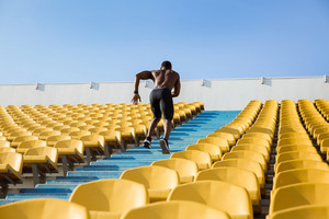 Back view of a young male athlete exercising by running upstairs at the stadium