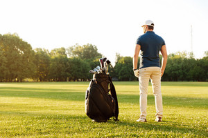 Back view of a young man standing on a green field with golf bag