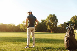 Back view of a young man with hands on hips standing on a green field with golf bag