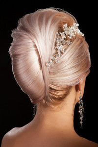 Back view of advanced creative hairstyle of one beautiful blonde woman. Studio shot.