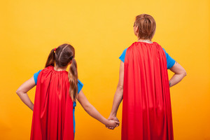 Back view of mother and her little girl dressed like superheros holding hands. .