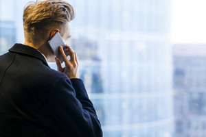 Back view of unrecognizable young white collar worker having phone conversation while enjoying picturesque view from office window