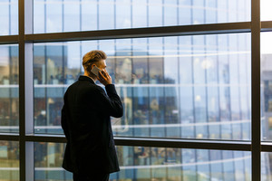 Back view of young businessman wearing suit standing at panoramic window while having project discussion with his colleague on smartphone