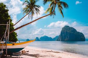 Banca boat on shore under palm trees. Tropical island scenic landscape. El-Nido, Palawan