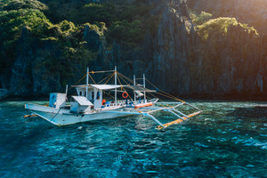 Banca local boat on turquoise water against huge limestone cliffs. Island hopping tour trip. Exploring Philippines summer vacation journey holidays. Marine National Park, Palawan