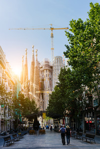 BARCELONA, SPAIN - April 24, 2018: View of the towers of the Sagrada Familia between the trees from the square with tourists, illuminated by the afternoon sun. April, 24, 2018