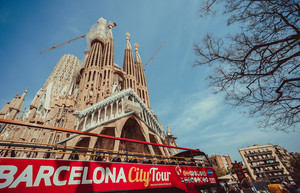 BARCELONA, SPAIN - April 25, 2018: Barcelona city tour touristic bus in front of famous Sagrada Familia Basilica yet not finished work of Catalan architect Antoni Gaudi