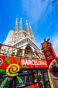 BARCELONA, SPAIN - April 25, 2018: Barcelona city tour touristic bus with tourists near famous Sagrada Familia Basilica. Unfinished work of Catalan architect Antoni Gaudi