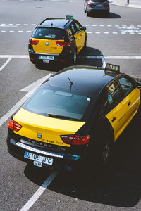 BARCELONA, SPAIN. April 26, 2018: Taxi at the road junction of the city of Barcelona in Spain. Classic taxi yellow and black. Hybrid car