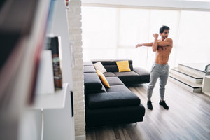 Bare chested young man stretching muscles before starting a workout routine. Handsome hispanic male athlete exercising for wellness in his living room. Latino people doing fitness and sport at home.