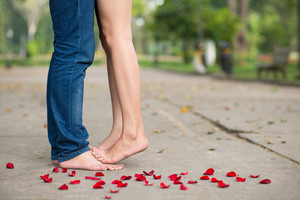 Bare feet of lovers among rose petals