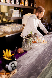 Barman adding cocktail ingredients. Barman in bar interior making alcohol cocktail.