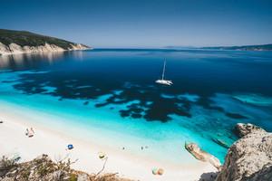 Beach leisure activity. Fteri bay, Kefalonia, Greece. White catamaran yacht in clear blue sea water. Tourists on sandy dream like beach near azure lagoon