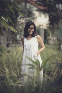 beakutiful asian woman wearing white dress standing in park