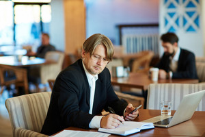 Bearded businessman in eyeglasses taking notes while working in comfortable restaurant, modern laptop, documents and notebook located on table