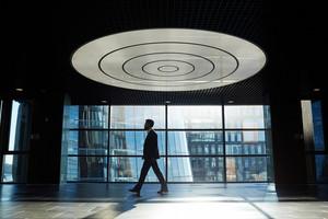 Bearded businessman wearing suit walking along modern office lobby, profile portrait shot