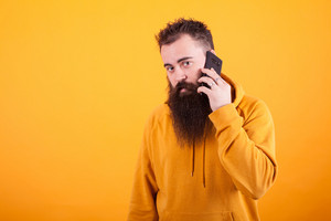 Bearded guy looking worried at the camera while talking on the phone over yellow background.