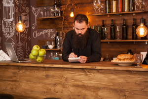 Bearded hipster bartender taking notes behind bar counter