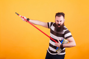 Bearded hipster in striped t-shirt using broom as if was a guitar over yellow background. Cool man. ,