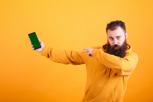 Bearded hipster in yellow hoodie pointing at phone over yellow background. Cheerful man . Handsome guy.