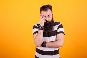 Bearded hipster young man thinking over yellow background in studio photo