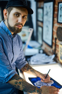 Bearded man in ball-cap making sketch of creative tattoo