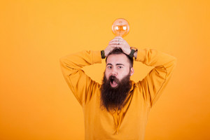Bearded man looking amazed with light bulb over his head in front of yellow background. Handsome man. Confident man.